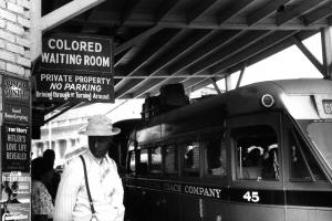 """A black and white photo of a black man standing in front of a sign that reads """"Colored Waiting Room"""" in front of a train."""